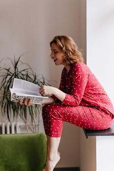 Het lachen het tijdschrift van de vrouwenlezing op blote voeten in de ochtend. binnen schot van mooie vrouw in pyjama zittend op de vensterbank.