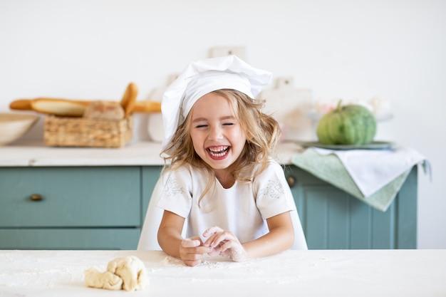 Het lachen meisje het spelen met deeg voor koekjes op keuken