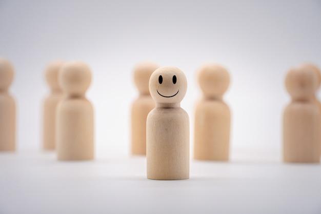 Het lachende gezicht op een houten menselijke icoon. concept voor de winnaar van de competitie.