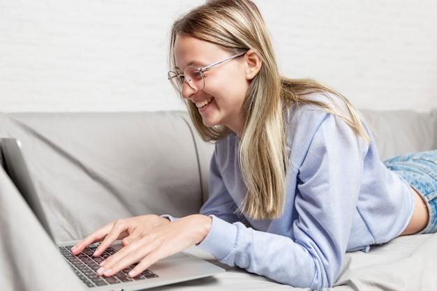 Het lachende jonge meisje met glazen ligt op de laag voor laptop. werken op afstand, onderwijs op afstand en bloggen.