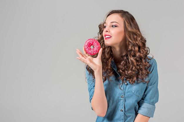 Het lachende meisje met ronde taart op grijze studiomuur