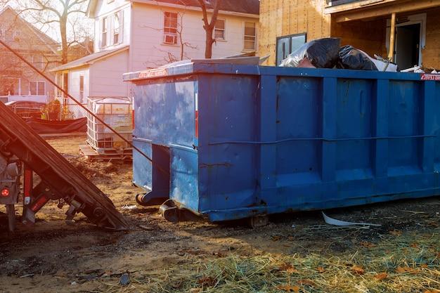 Het laden van de afvalcontainer oud en gebruikt bouwmateriaal in de nieuwe bouwplaats.