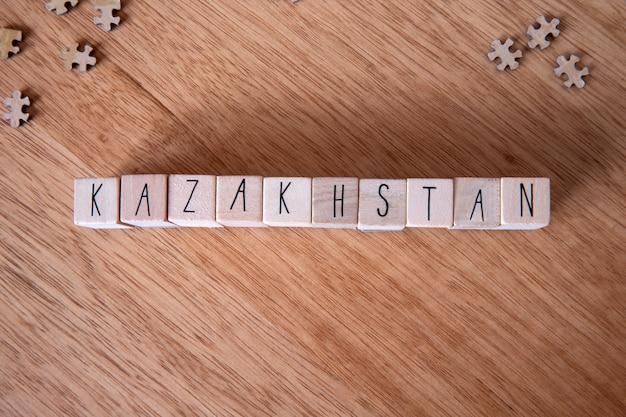 Het land kazachstan geschreven op houten kubussen op houten achtergrond,