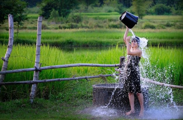 Het landelijke meisje neemt een douche van een traditioneel grondwater op platteland.