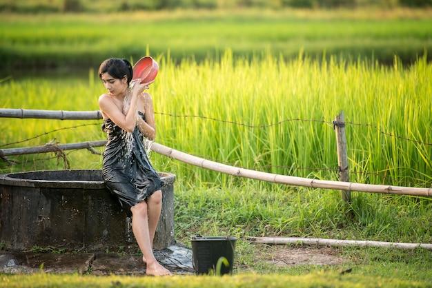 Het landelijke meisje neemt een douche van een traditioneel grondwater