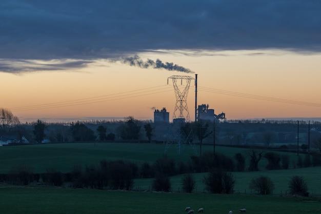 Het landschap dat van het vroege ochtendplatteland aan fabriek in de verte met zonlicht kijkt dat de rook verlicht.