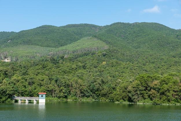 Het landschap naast het stuwmeer is blauwe lucht, witte wolken, groene bergen en helder water