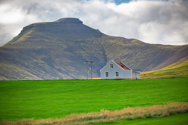 Het landschap van bergen met een wit opruimen ijslands huis