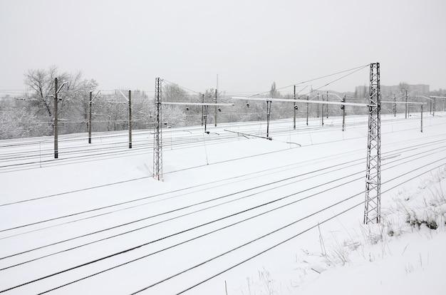 Het landschap van de de winterspoorweg, spoorwegsporen in het snow-covered industriële land