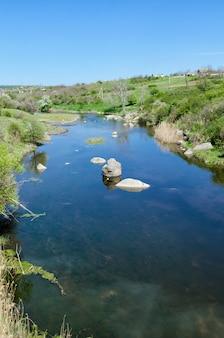 Het landschap van de plattelandsrivier in vroege lentetijd.