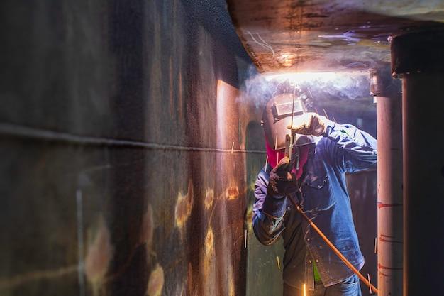 Het lassen van de metalen boog van de mannelijke werknemer maakt deel uit van de pijpleidingconstructie van de machinetank, de aardolie- en gasopslagtank in besloten ruimtes.