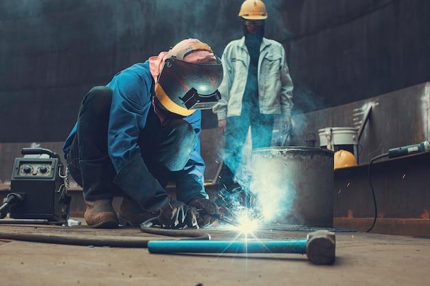 Het lassen van het metalen boogdeel van de mannelijke werknemer in de pijpleidingconstructie van het tankmondstuk, aardolie, olie en gasopslag, toptankdak