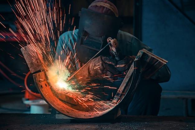 Het lassen van stalen constructies en heldere vonken in de staalbouw. blauwe toon