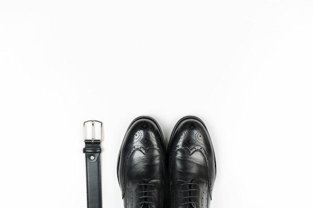 Het lederen schoenen en riem van mannen op een witte achtergrond