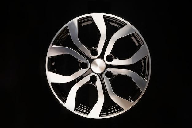 Het legeringswiel van de nieuwe auto, close-up op een zwarte ruimte