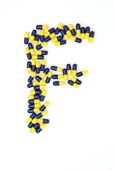 Het letter f alfabet gemaakt van medische capsules