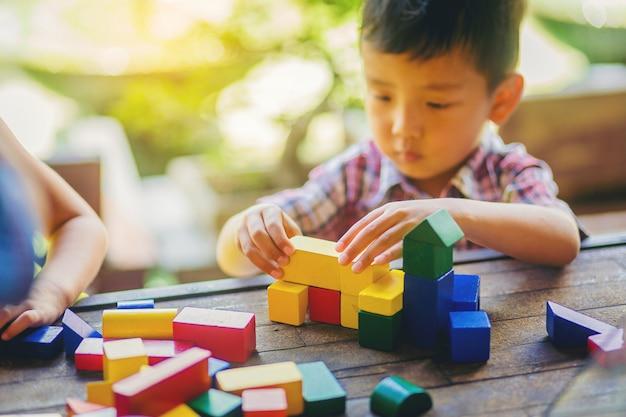 Het leuke aziatische jongen spelen met kleurrijk houten blok. opleiding