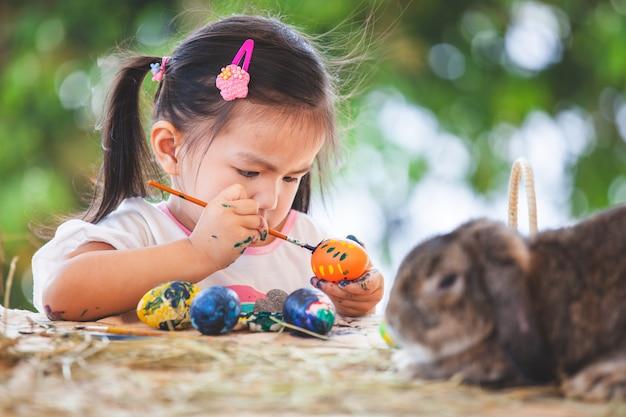 Het leuke aziatische kindmeisje die en op paaseieren trekken schilderen treft voor pasen-dag voorbereidingen