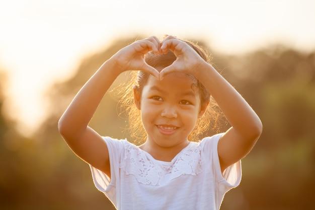 Het leuke aziatische kindmeisje die hartvorm maken met dient het gebied met zonlicht in