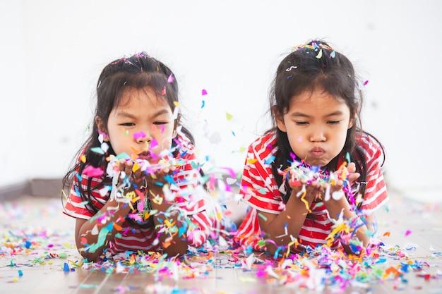 Het leuke aziatische kindmeisje en haar zuster spelen samen met kleurrijke confettien om in partij te vieren