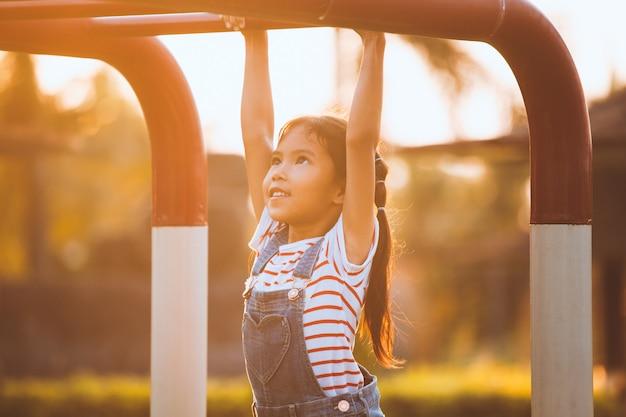 Het leuke aziatische kindmeisje hangt de bar door haar hand aan oefening in de speelplaats te hangen