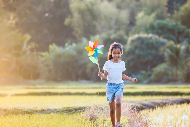 Het leuke aziatische kindmeisje loopt en speelt met het stuk speelgoed van de windturbine met pret op het padiegebied