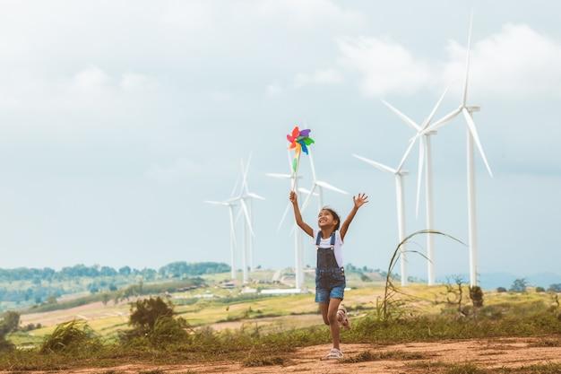 Het leuke aziatische kindmeisje loopt en speelt met het stuk speelgoed van de windturbine op het gebied van de windturbine