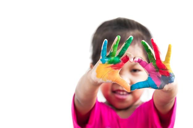 Het leuke aziatische kindmeisje met geschilderde handen maakt hartvorm op witte achtergrond