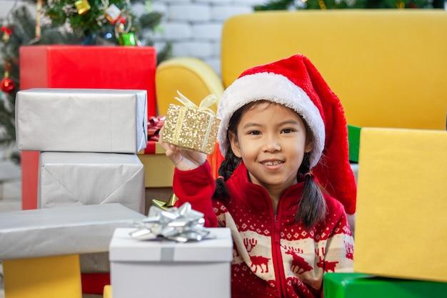 Het leuke aziatische kindmeisje met giftdozen en het verfraaien voor viert op kerstmisfestival
