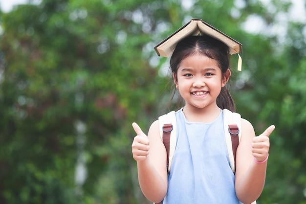 Het leuke aziatische kindmeisje met schooltas zette een boek op hoofd en liefde om naar school te gaan