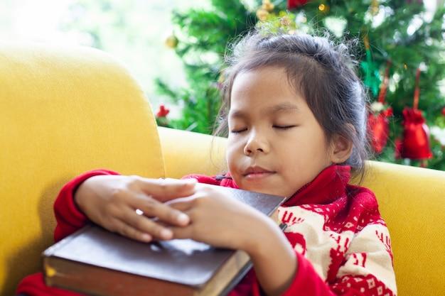 Het leuke aziatische kindmeisje slaapt en koestert een boek in kerstmisviering