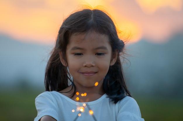Het leuke aziatische kindmeisje speelt met vuursterretjes op het festival in het padieveld