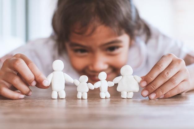 Het leuke aziatische kindmeisje spelen met de gelukkige familie van de plasticineklei met pret. gelukkig familieconcept.