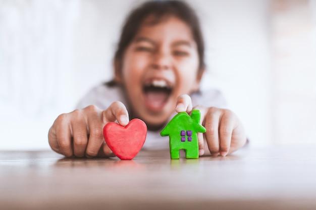 Het leuke aziatische kindmeisje spelen met het huis en het hart van de plasticineklei met pret.
