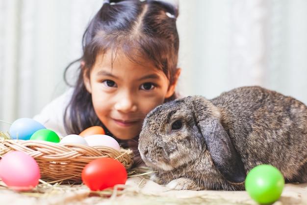 Het leuke aziatische kindmeisje spelen met het leuke konijn van holland met liefde en tederheid in feestelijke pasen
