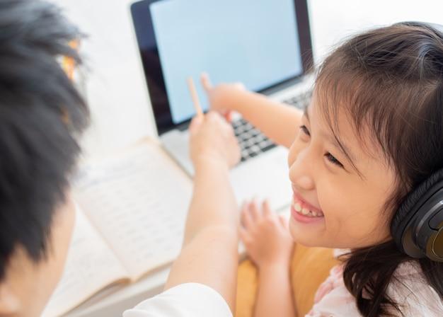 Het leuke aziatische meisje en haar notitieboekje van het leraarsgebruik voor het bestuderen van online les tijdens huisquarantaine.