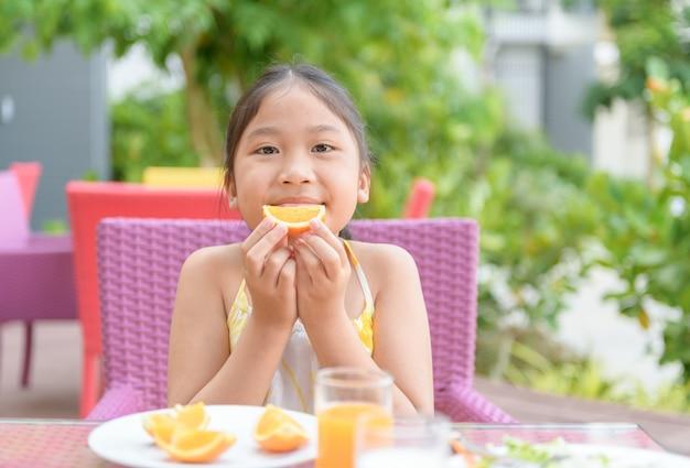 Het leuke aziatische meisje geniet van om verse sinaasappel op ochtend te eten,