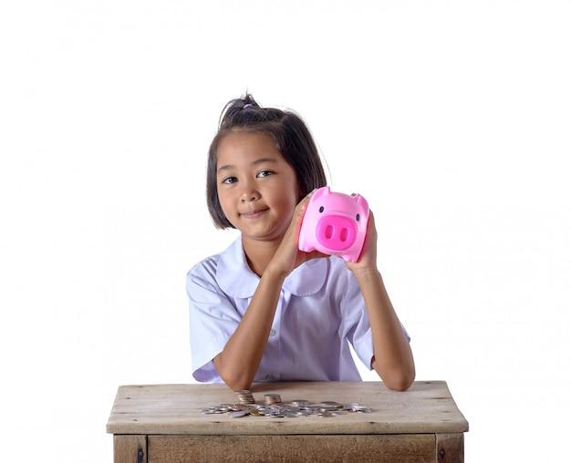 Het leuke aziatische meisje heeft pret met geïsoleerd spaarvarken op witte achtergrond
