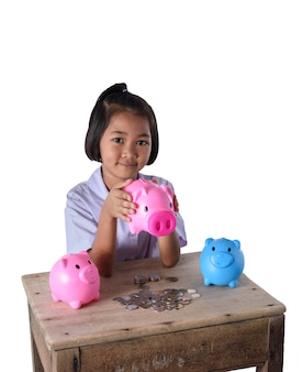 Het leuke aziatische meisje heeft pret met veel die spaarvarken op witte achtergrond wordt geïsoleerd