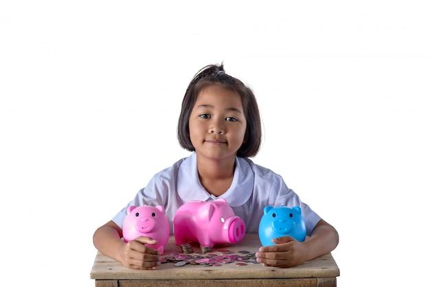 Het leuke aziatische meisje heeft pret met veel geïsoleerd spaarvarken op wit