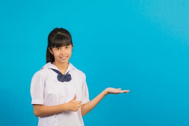 Het leuke aziatische schoolmeisje doen duimen op gebaar en opent uw hand op het blauw.