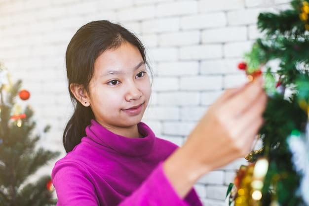 Het leuke aziatische tienermeisje verfraait kerstmisboom voor viert op kerstmisfestival