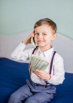 Het leuke babyjongen spelen met heel wat geld zoals het spreken op telefoon, amerikaanse honderd dollars contant geld. amerikaanse honderd dollar in contanten.