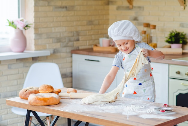 Het leuke babymeisje in een chef-kokkostuum kookt in de keuken