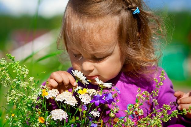 Het leuke babymeisje ruikt bloemen, de zomertijd