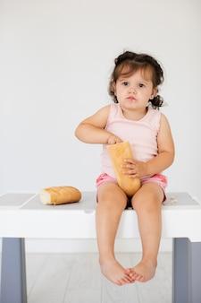 Het leuke babymeisje spelen met brood