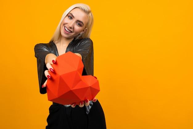 Het leuke blonde meisje houdt een 3d hartvorm op een gele ruimte met exemplaarruimte