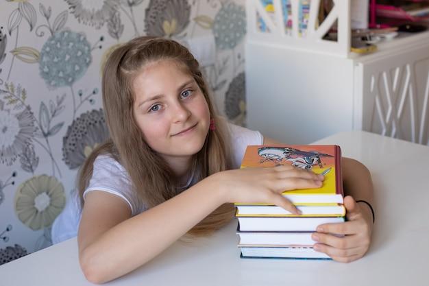 Het leuke blonde meisje houdt een stapel kleurrijke boeken glimlachend zij is gelukkig de lezing van de conceptenvrije tijd