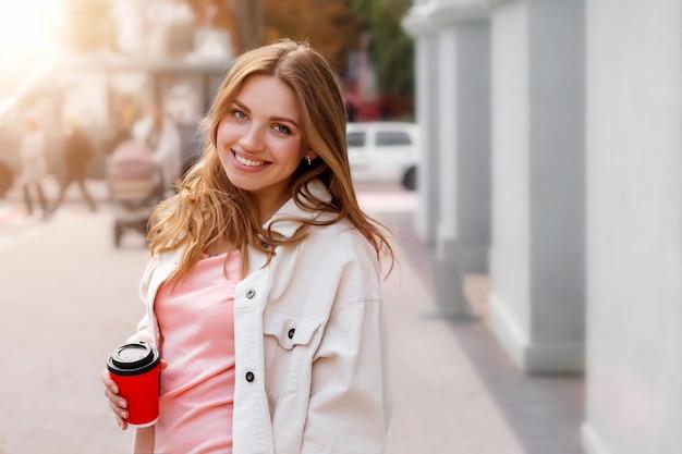 Het leuke blondemeisje loopt in de stad met een kop van koffie en het glimlachen