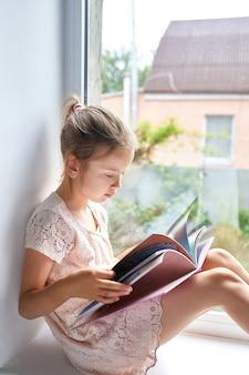 Het leuke boek van de meisjeslezing thuis, bij vensterbank